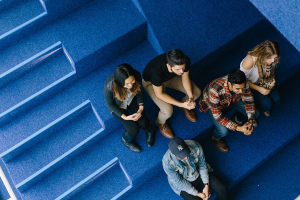 Aerial view of students sitting on blue stairs at the Sandbox.