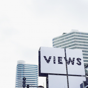 "A billboard showcasing the word ""Views"" amongst skyscrapers."
