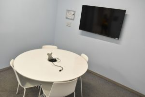A Collaborative & Group Work Room with a white table, four chairs and TV screen.