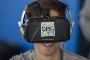 Student trying on virtual reality goggles at the DME